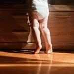 baby standing on a hardwood floor