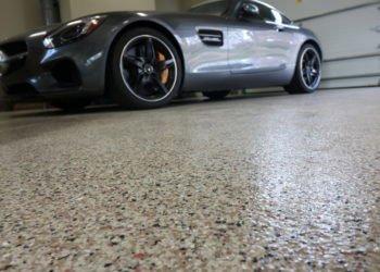 a black car on a parking garage with concrete epoxy floor